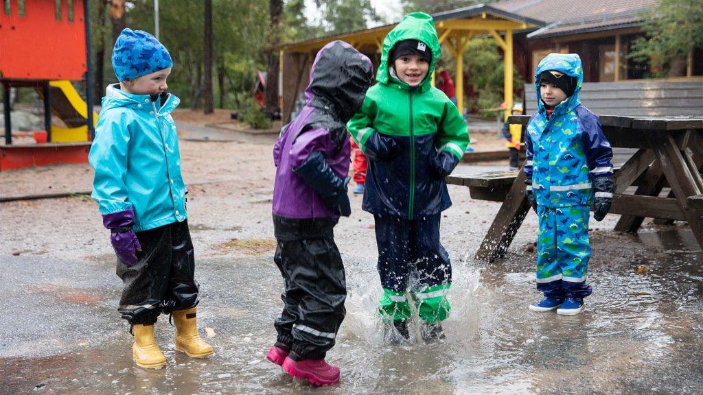 Fyra barn är i skolgården och har regnkläder på sig, de hoppar i en stor vattenpöl