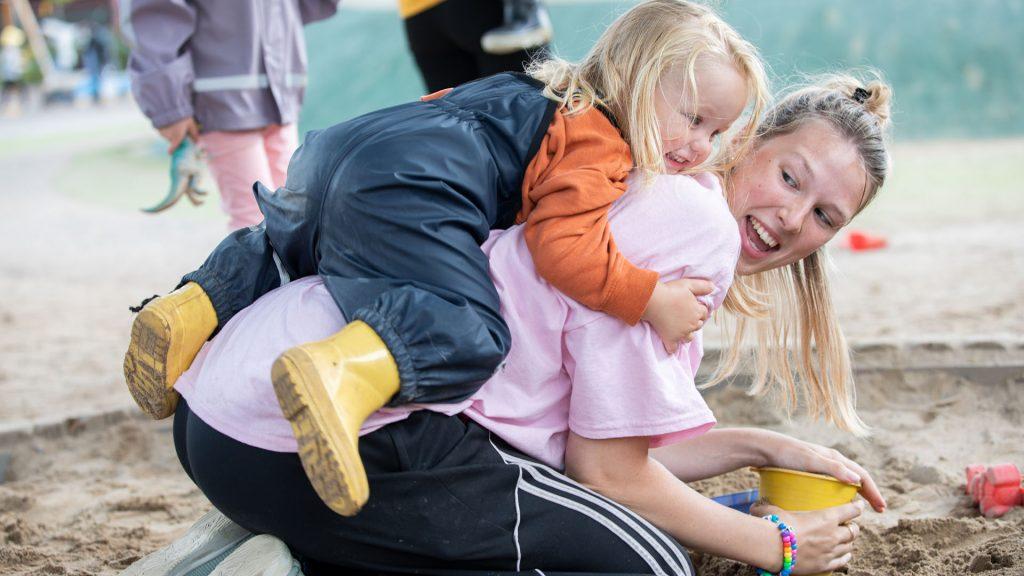 Ett barn hänger på lärarens rygg medan de leker i en sandlåda