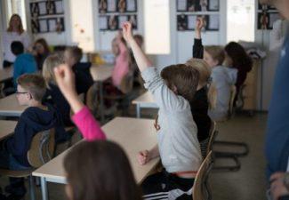 Barn i klassrum som räcker upp handen