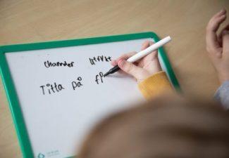 Barn skriver med på liten whiteboard tavla