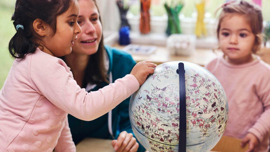 Två barn pekar och upptäcker ett jordklot markerade med djur på.