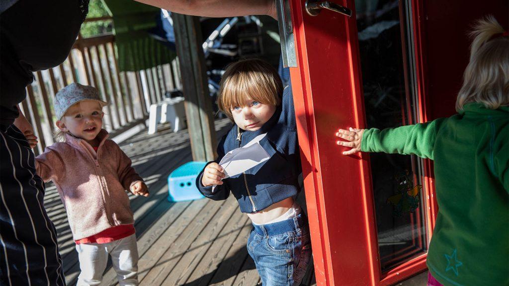 Tre barn står intill ingången av skolan, en lärare håller upp en dörr medan ett barn springer in