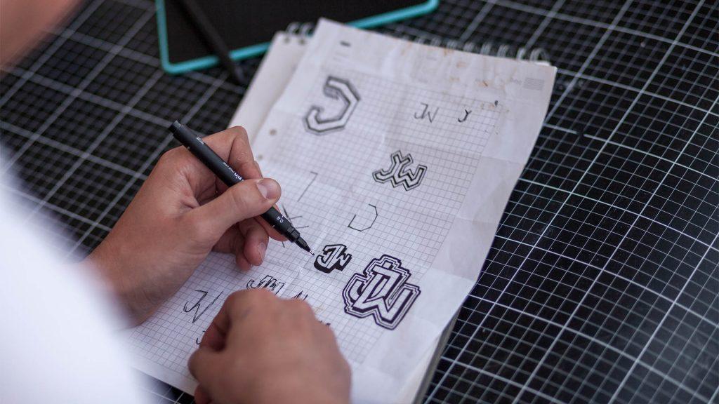 """Person ritar logotyper av initialerna """"JW"""""""