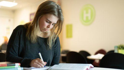 En elev på Hermods skriver anteckningar medan hon läser bok