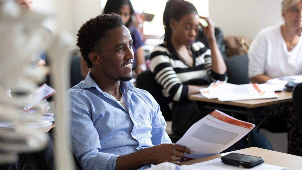 En elev sitter på lektion och håller häftade papper