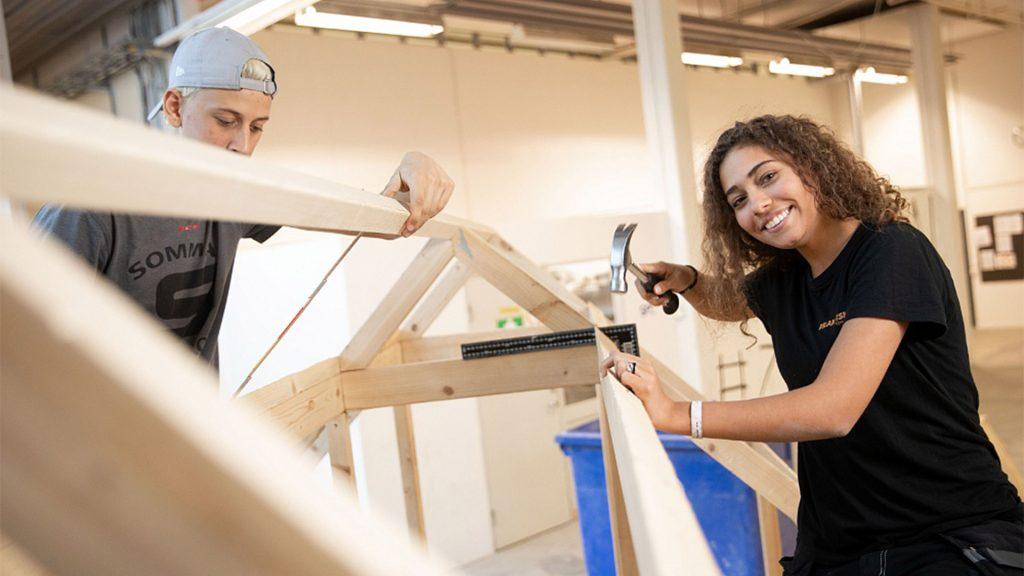 Två elever på Praktiska gymnasiet bygger ett trähus, en av de håller i en hammare medan den andra mäter