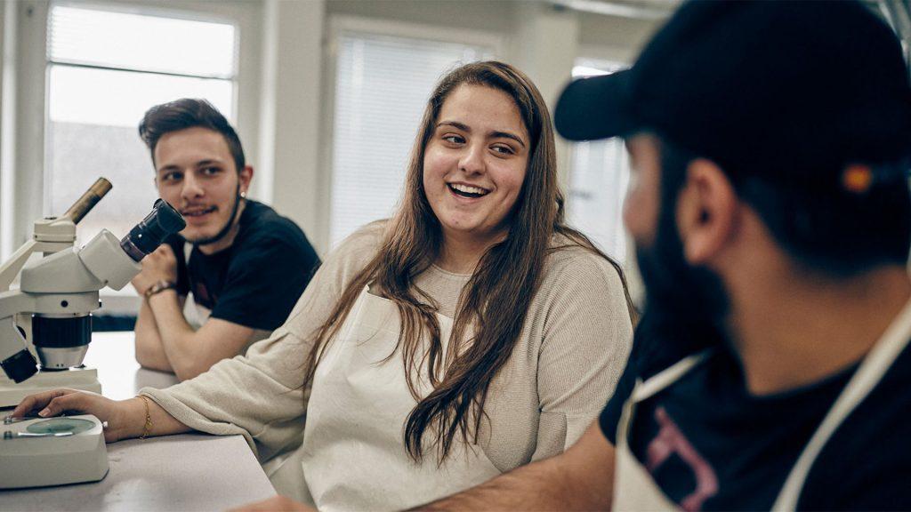 Tre elever sitter på rad i ett klassrum, en av eleverna håller på ett mikroskop
