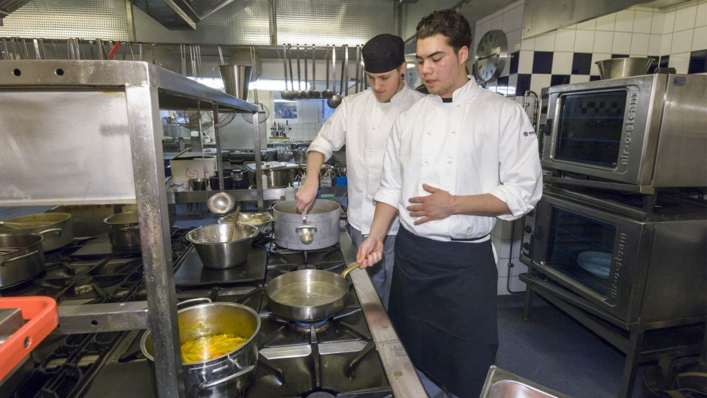 Två elever står i ett kök och lär sig om matlagning.
