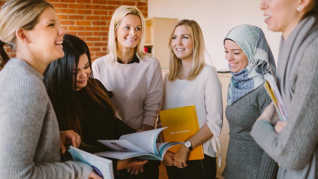"""Elever och lärare står i en cirkel nära intill varandra, en håller en bok och en gul mapp som står """"vårdyrkeshögskolan"""""""