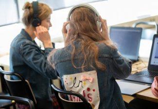 Två elever sitter bredvid varandra i klassrummet, de har båda på sig hörlurar och tittar på en datorskärm