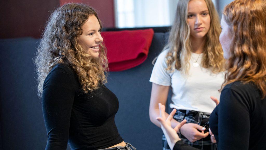 Tre elever från Rytmus står och snackar i en korridor
