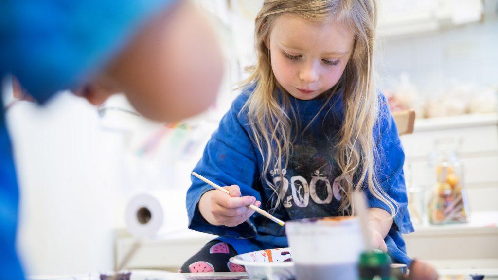 Litet barn målar med pensel