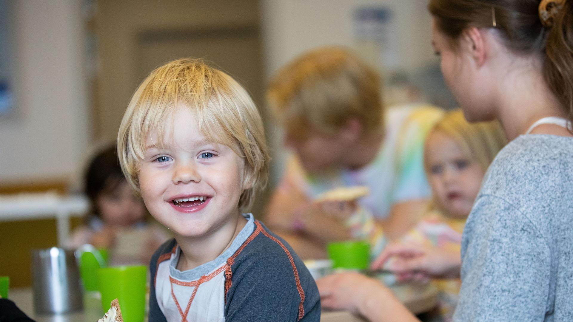 En pojke håller knäckebröd och ler mot kameran