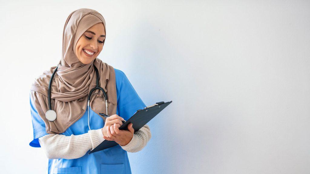 Sjuksköterska med hijab ler och skriver på ett papper, hon har ett stetoskop runt halsen