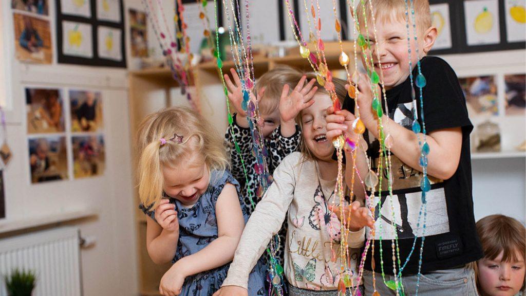 Flera barn ler och skrattar medan de leker med dörrdekorationen