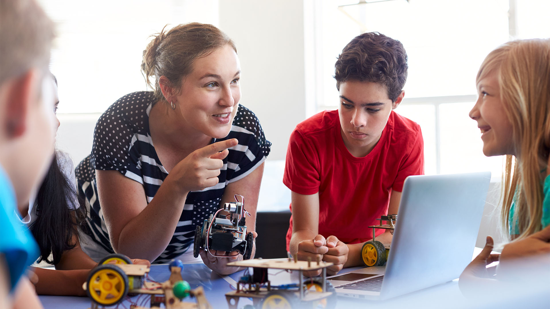 Elever i grundskola ska lära sig koda små maskiner. De står i en cirkel medan läraren förklarar framför hennes dator