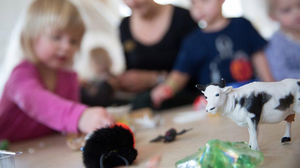 Fokus på leksaksko, i bakgrunden är barn som leker