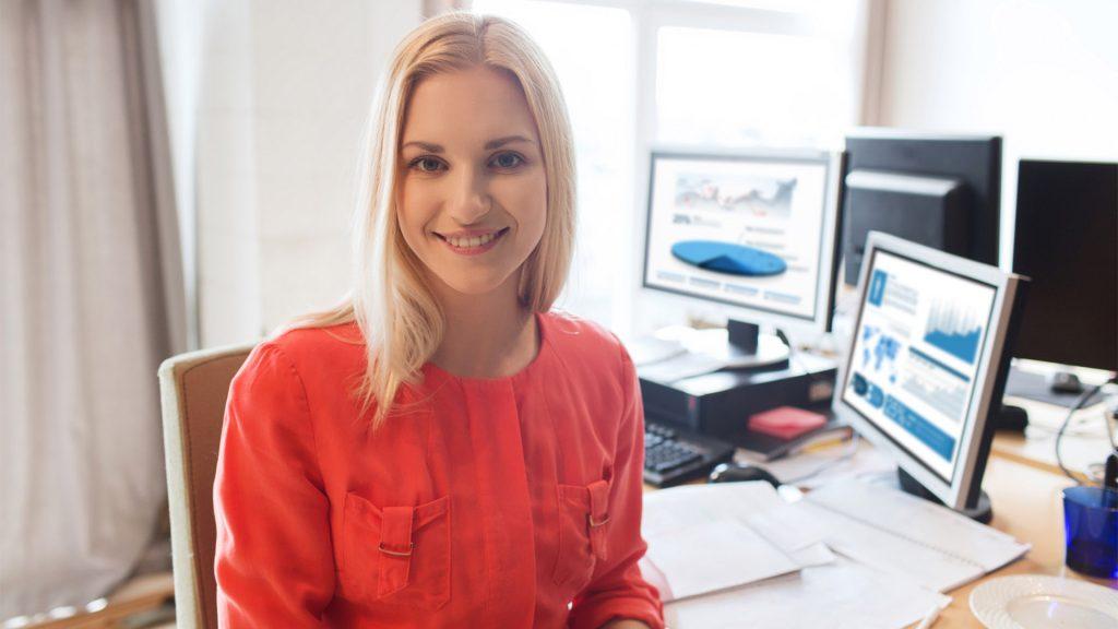 En kvinna ler mot kameran, hon sitter i ett kontorsmiljö och bakom henne är flera datorskärmar och papper på bordet