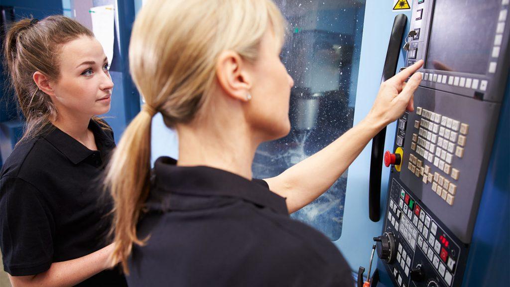 En kvinna pekar vid en skärm och lär kvinnan bredvid henne om CNC maskiner
