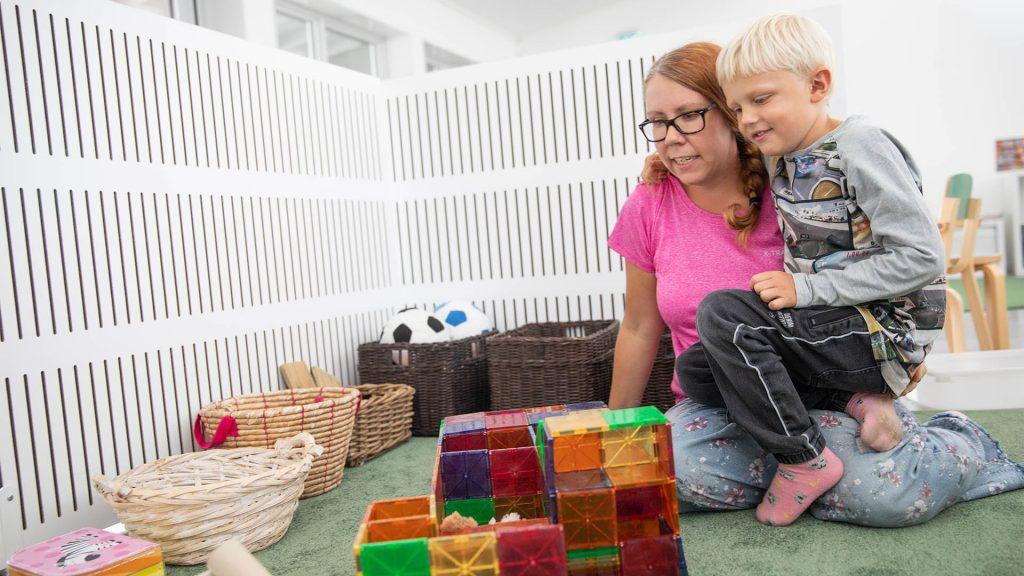 En lärare sitter på golvet och håller ett barn och verkar förklara något gällande leksaker och ordning