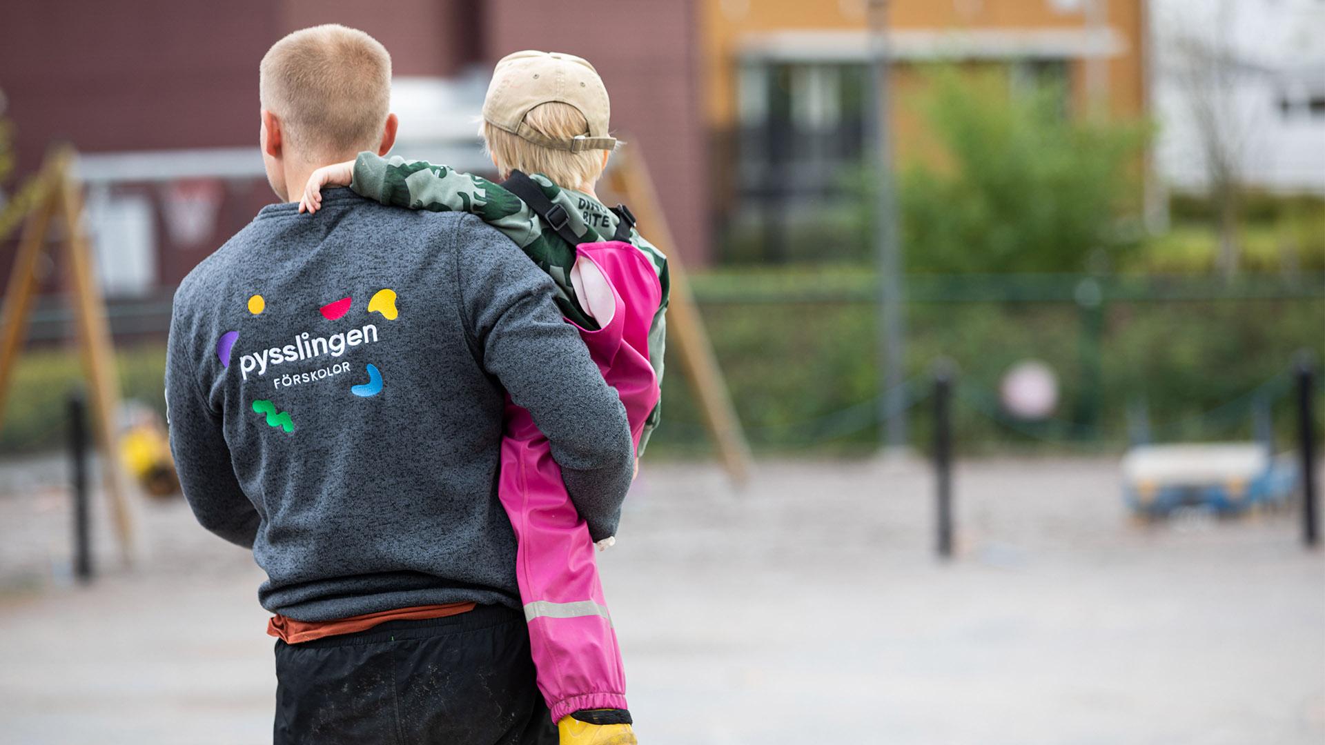 """Vuxen som håller upp ett barn i en skolgårdsmiljö. Vuxens tröja står det """"pysslingen skolor"""""""
