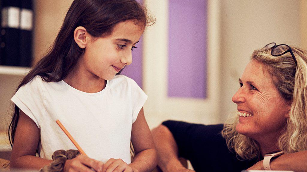 Lärare sitter på hut och ler upp åt eleven som sitter i sin skolbänk och skriver, de håller ögonkontakt