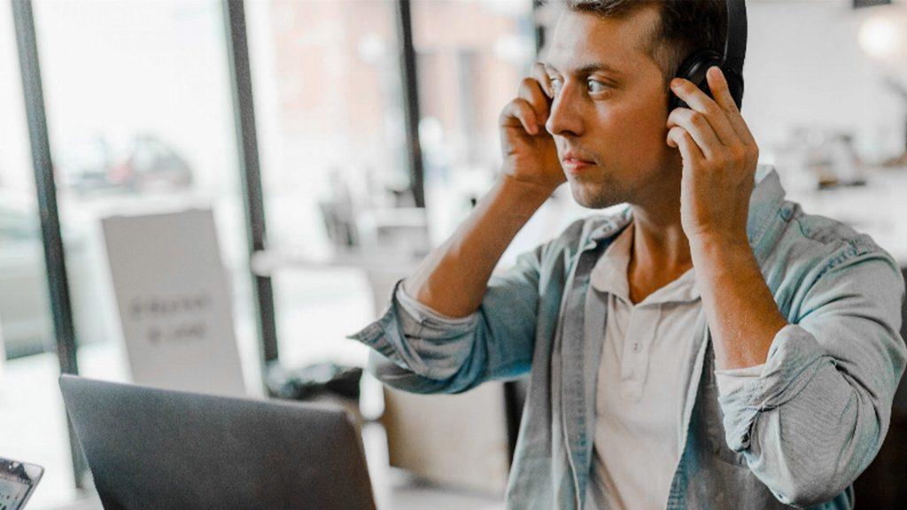 Person sitter i café liknande miljö och har en dator framför sig, han lyssnar på musik med sina lurar och tittar ut