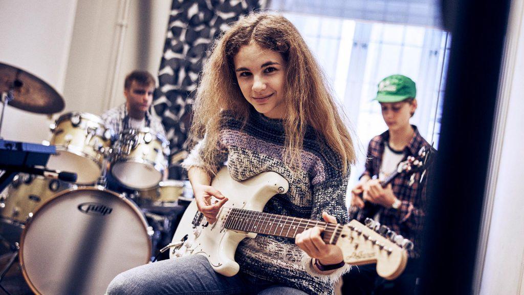 En person spelar elgitarr och ler mot kameran, i bakgrunden sitter en person vid trummorna och en person med bas