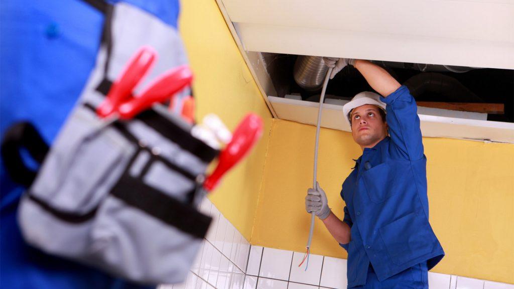 En person står och drar ner en kabel från taket