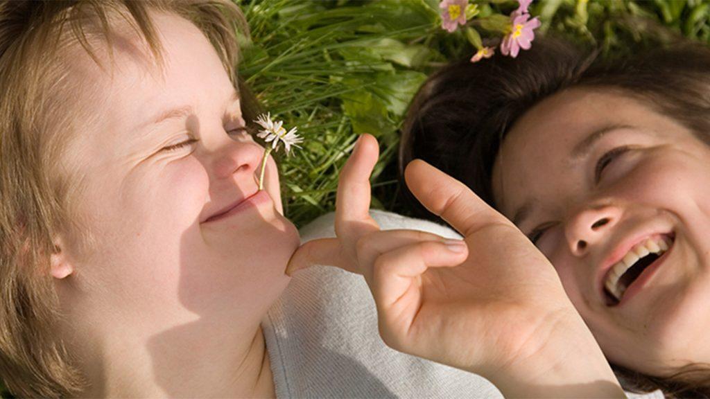 Två personer ligger i en gräs äng, en av de har en liten blomma i munnen och ser glad ut