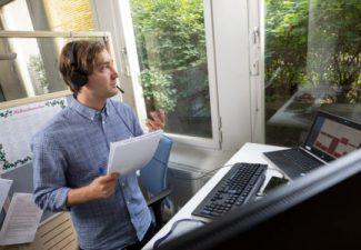 Lärare med hörlurar och mikrofon som undervisar på distans