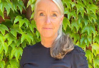 Porträttbild på Maria Bivesjö framför en grön häck