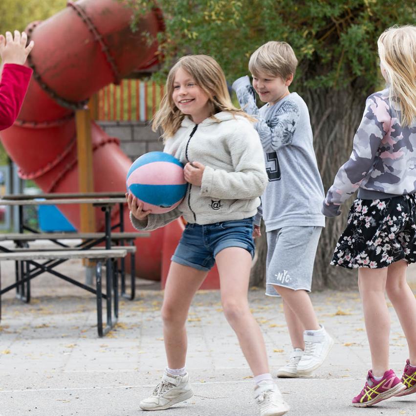Barn leker vid en skolgård, en flicka håller i en basketboll och en pojke hoppar