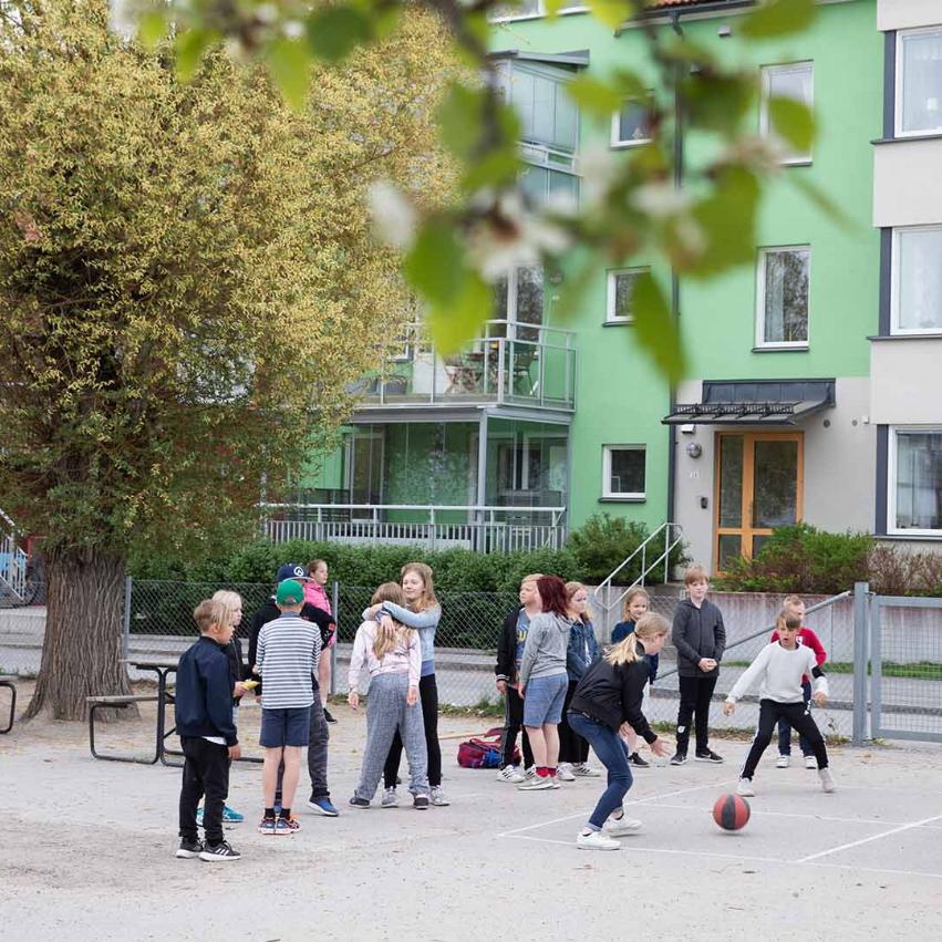 Flera barn befinner sig i en skolgård, några barn spelar med en boll på marken
