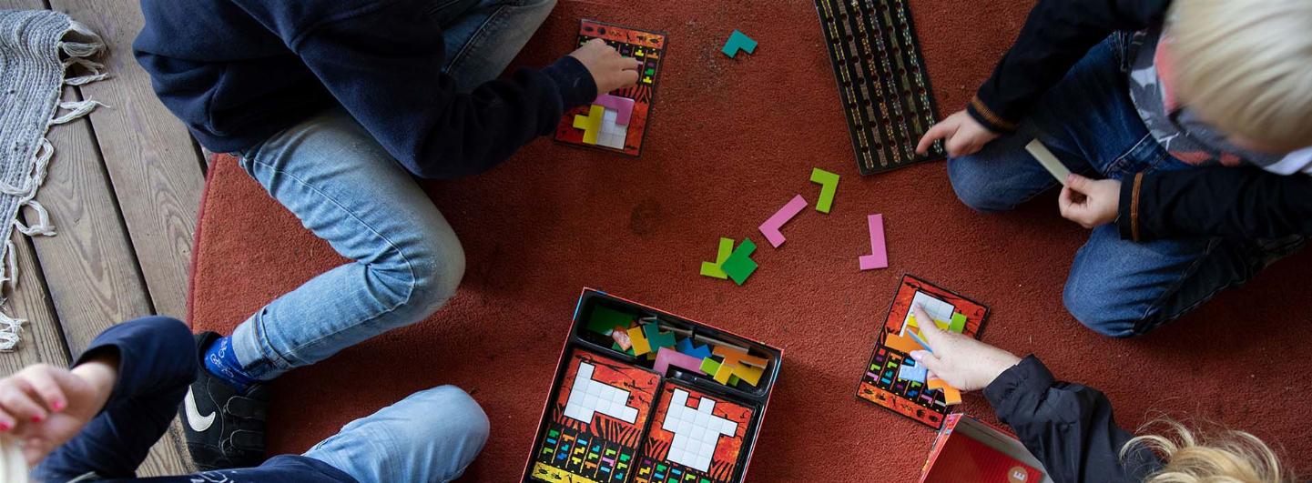 Fyra barn sitter ner vid en röd matta och lägger ut tetris-liknande av ett pussel
