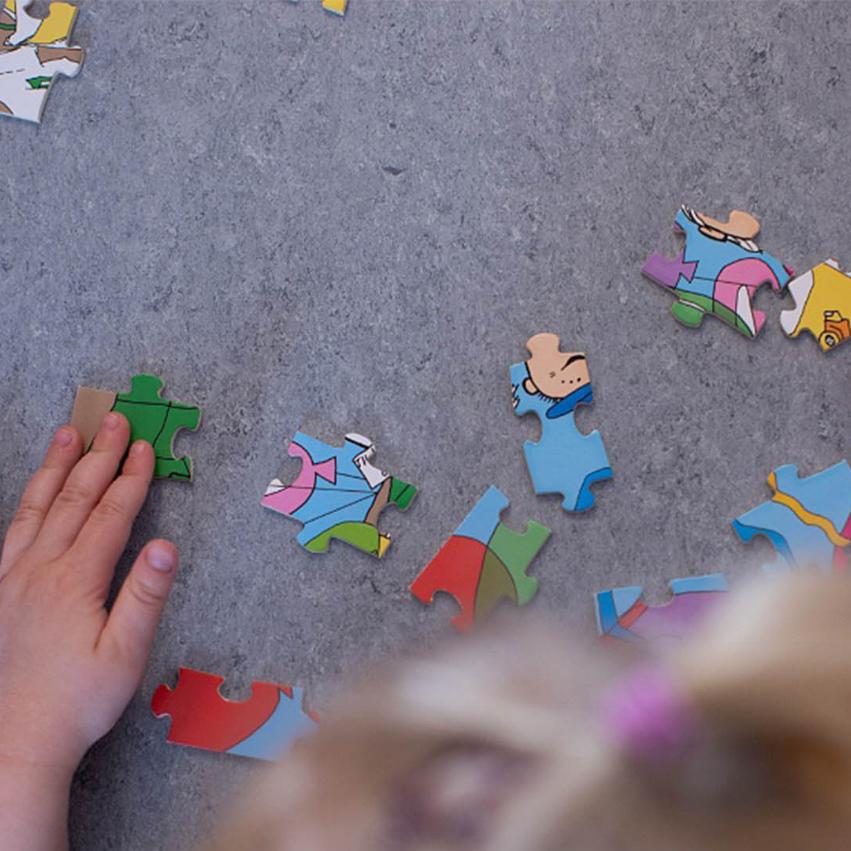 Ett barn lägger ut pussel på golvet