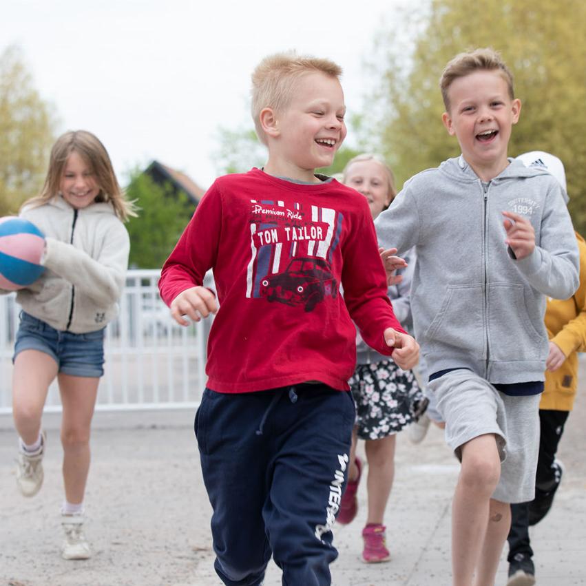 Barn i skolgård spelar basket och springer mot kameran