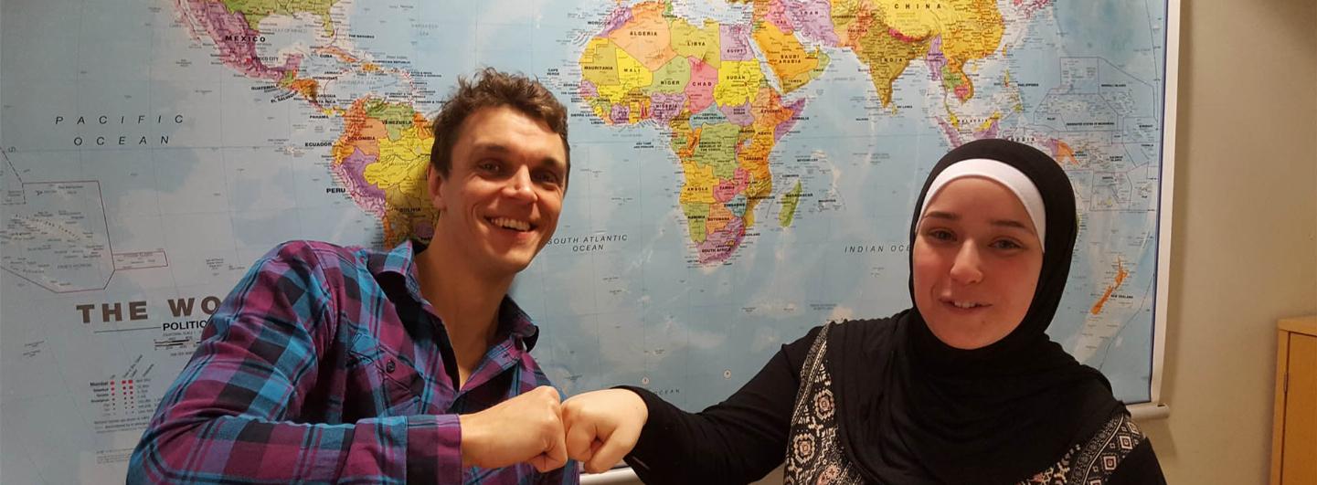 Två personer ger varandra en näve till varandra (en fistbump) och ler mot kameran