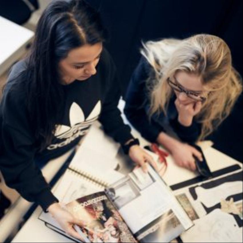 Elev håller i en tidning medan lärare bredvid henne lyssnar och hjälper henne