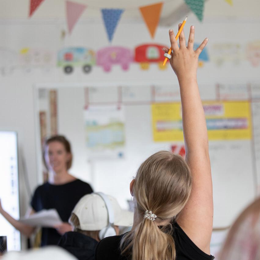 Elev räcker upp handen i en klassrumsmiljö