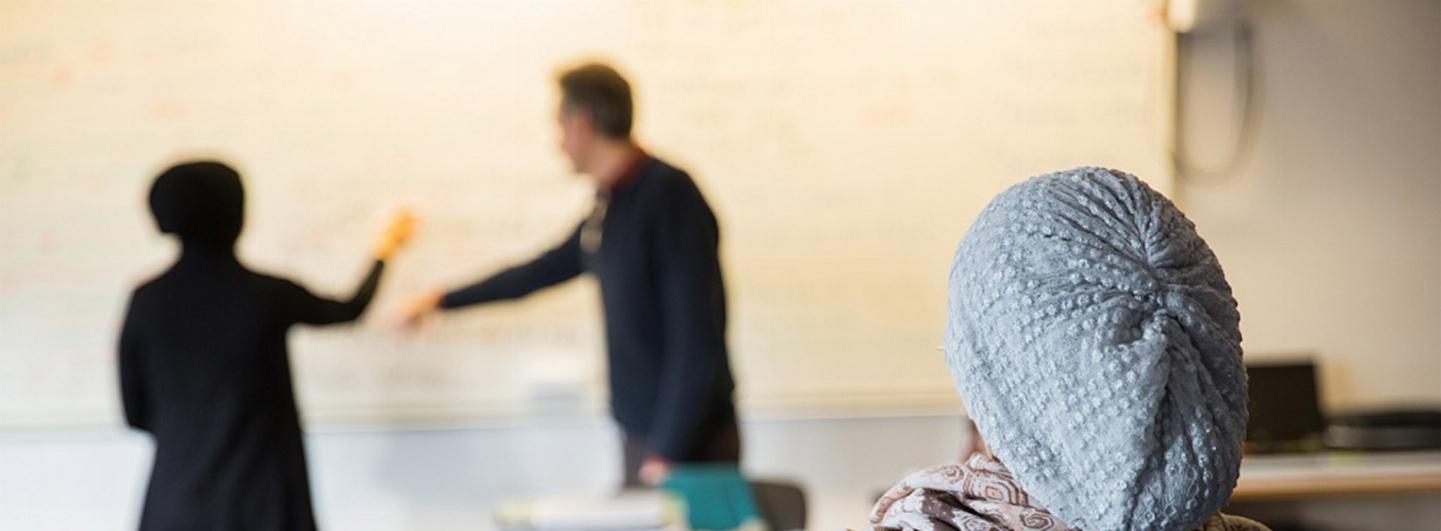 En elev som lyssnar på lektion. Framför de är en whiteboard, där står två personer och ritar och diskuterar