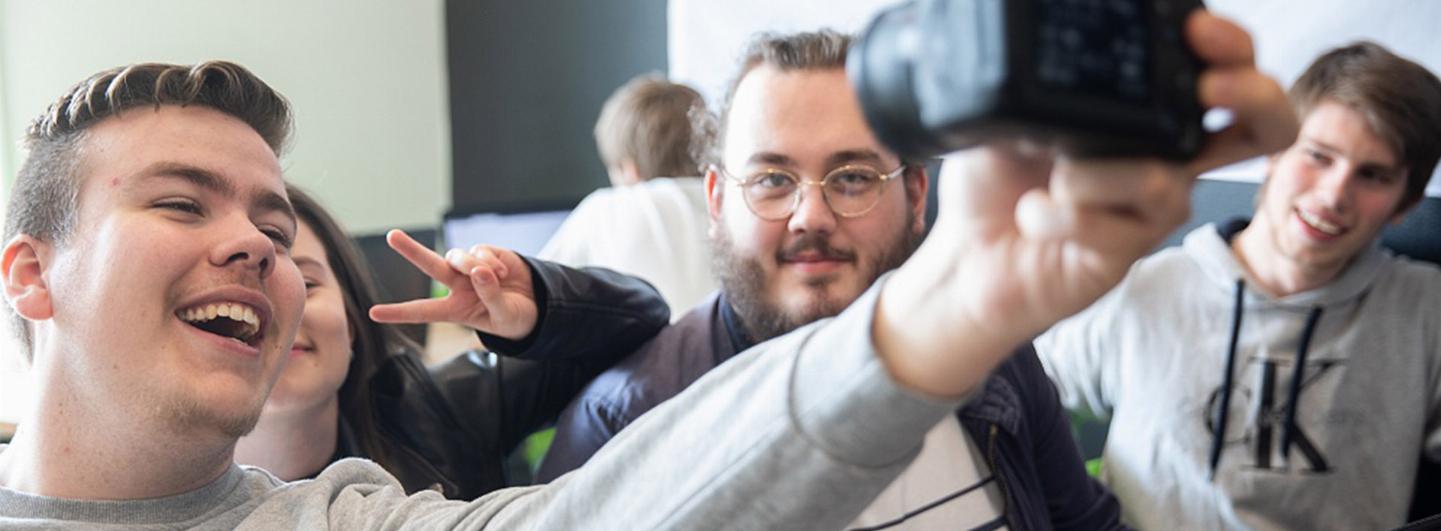 Elev håller upp systemkamera och ska ta ett självporträtt (en selfie) med sina vänner