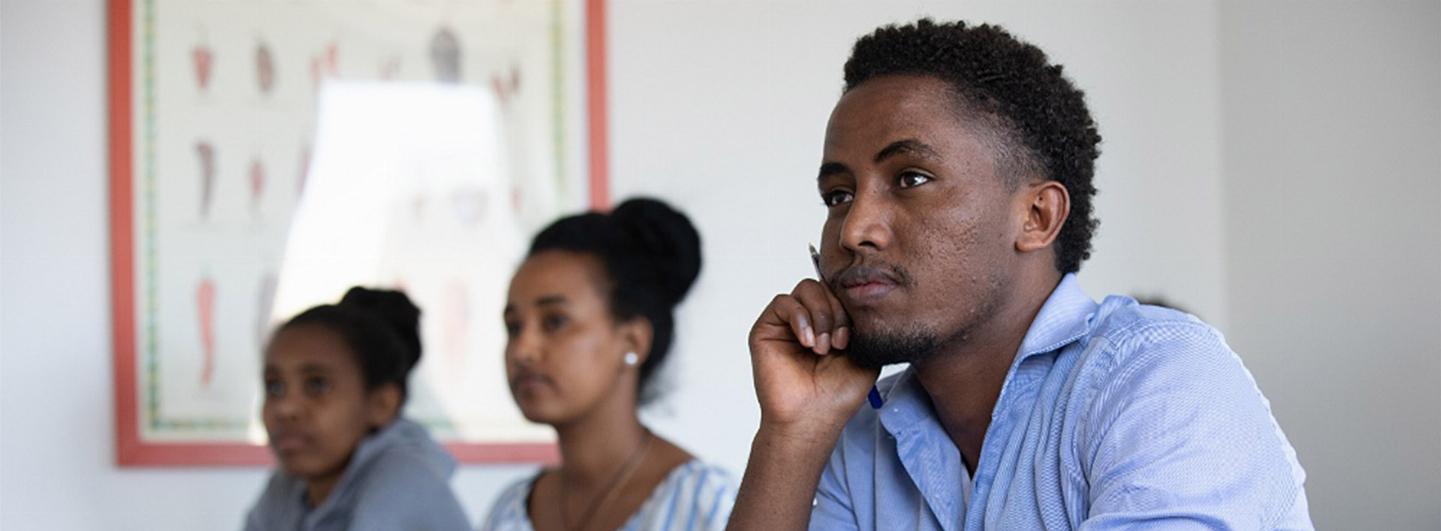 Elev i fokus sitter fundersam och lyssnar på lektion