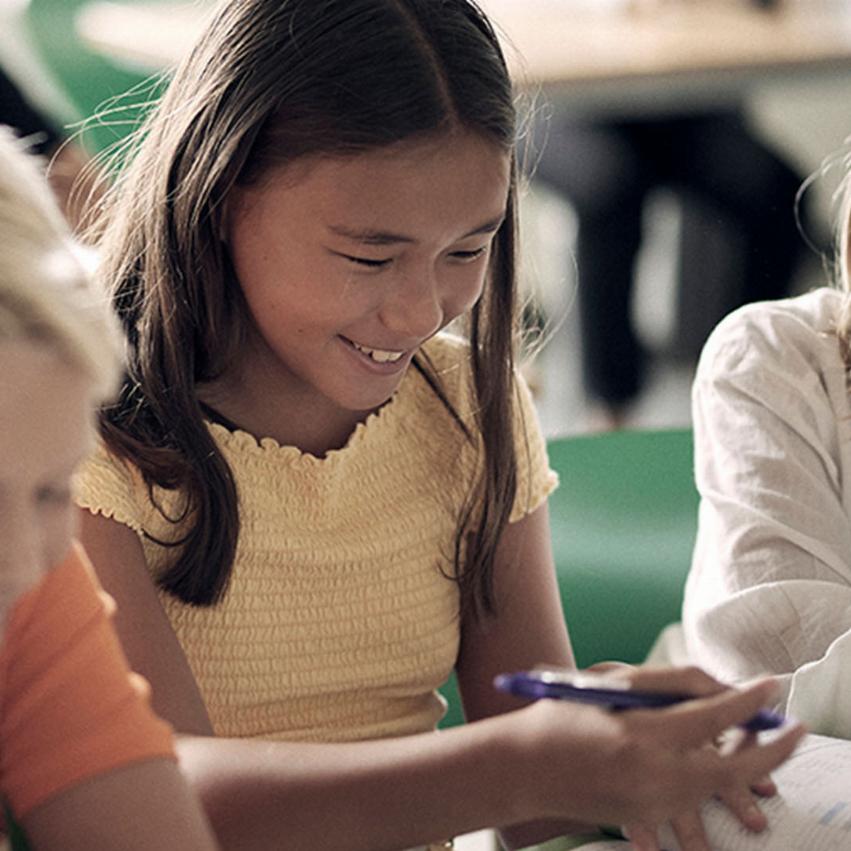 Tre elever sitter på rad i ett klassrum och ser glada ut.