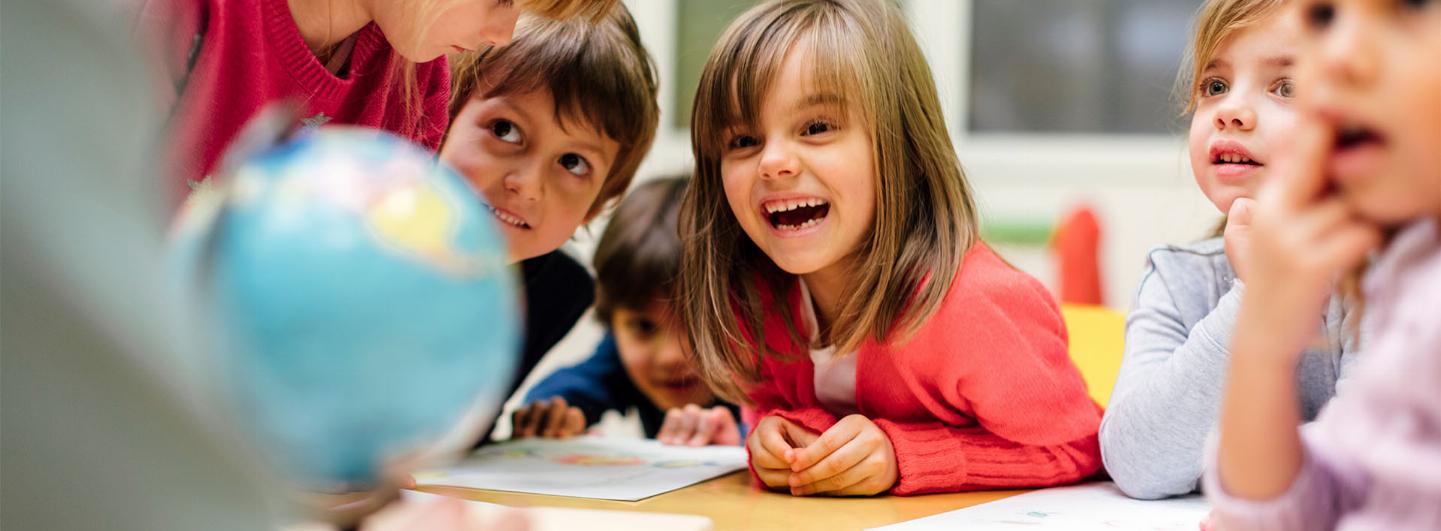 Flera små-barn sitter bredvid varandra vid ett barn. Ett barn i mitten ser extra glad ut av vad läraren gör
