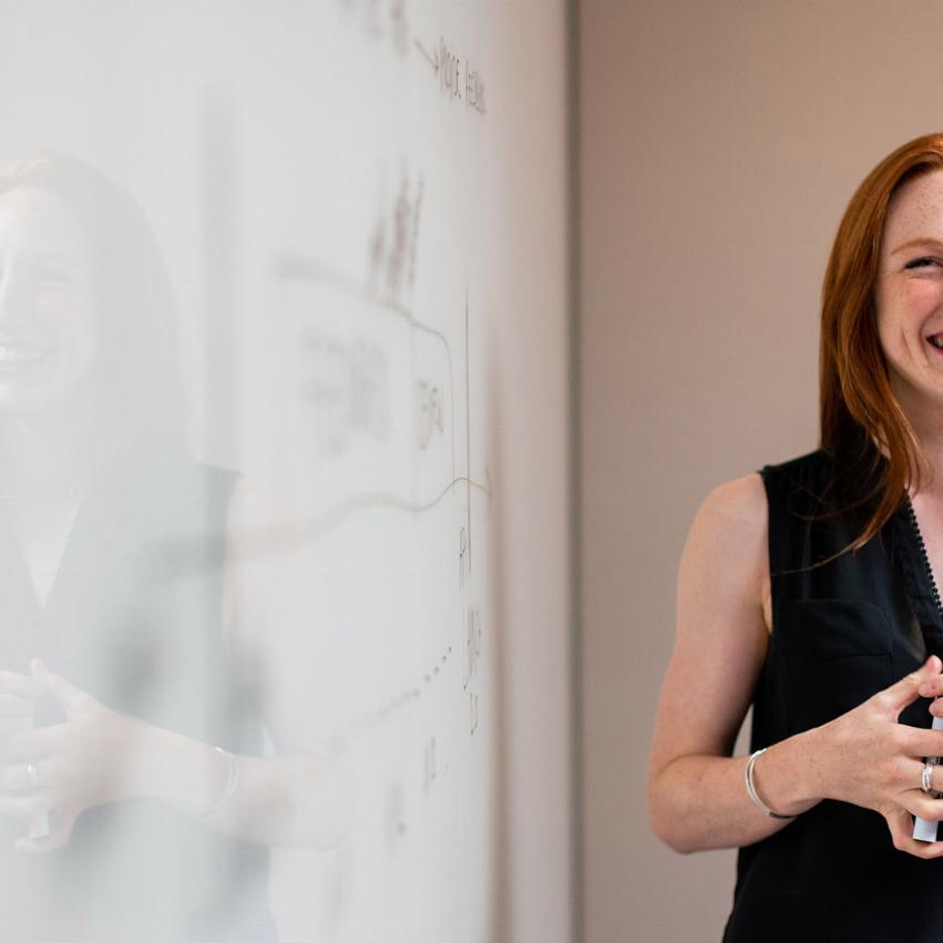 Kvinna står vid en whiteboard-tavla och ser glad ut