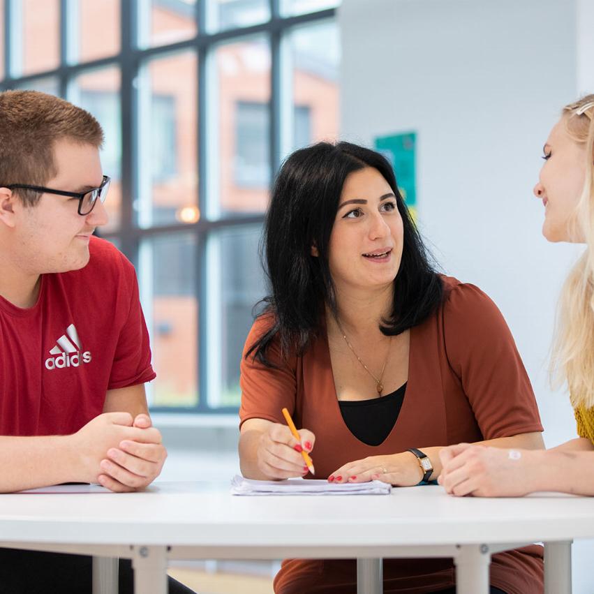 Tre personer sitter runt ett bord, personen i mitten pratar med en person som skrattar. Den andra personen lyssnar