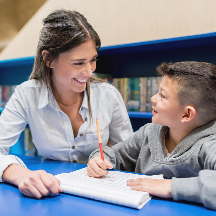 Lärare och ung elev sitter i ett bibliotek, den unga pojken skriver i hans anteckningsbok och läraren ler mot honom.