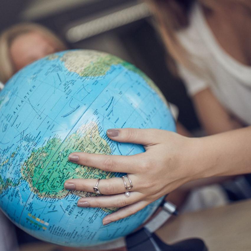 Hand på ett jordklot som liknar en världskarta