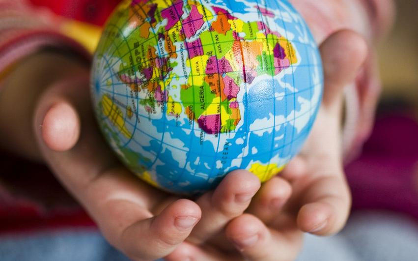 Ett leksaks-jordklot som hålls av ett litet barns händer